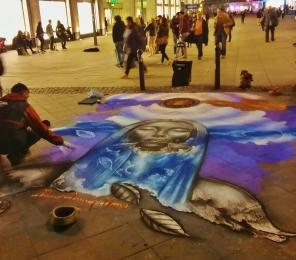 Taiteilija duunissa Alexanderplatzin kulmilla.