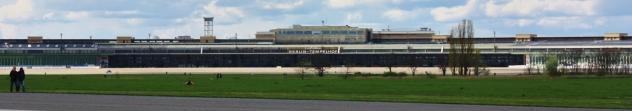 En tiedä, mistä kohtaa on mitattu, mutta puolikaaren muotoisen terminaalin/lentokonehallin pituus on kuulemma 1,2km.